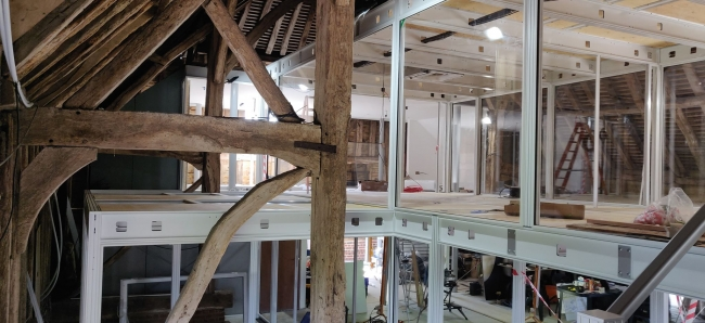 Modular two storey structure inside a 700 year old barn
